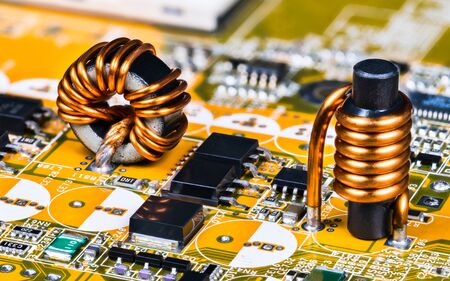 Toroidal and cylindrical inductor on circuit board of computer mainboard detail. Soldered induction coils with copper wire winding. Surface mount technology of micro chips, transistors and capacitors.