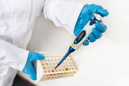 Scientist with pipette in hand dripping fluid to glass test tubes in plastic rack on white. Precise laboratory tool for measuring liquids volume in biology, chemistry or medicine. Vaccine development.