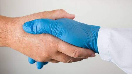 Shaking hands of healthcare professional with sick patient during COVID-19 pandemic. Safe handshake closeup on white background. Hand in blue protective glove and unprotected. Symbolic help or thanks. Zdjęcie Seryjne