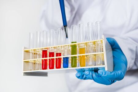 Researcher dripping blue fluid into glass test tubes in plastic rack by pipette. Close-up of pipetting. Scientist in white protective wear and glove holding in hand lab equipment with colored liquids. Zdjęcie Seryjne