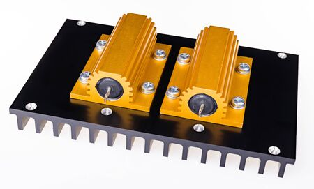 Two yellow power resistors bolted on black anodized aluminum heat sink on white background. Close-up of passive two-terminal electric components encased in golden aluminium outer case on metal cooler.