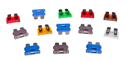 Colored automotive blade type fuses set isolated on white background. Collection of plastic current limiters with two metal prongs. Electrical safety device used to overcurrent protect in cars wiring.