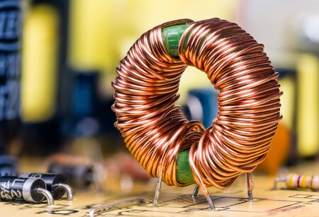 Induction coil with copper wire winding soldered on printed circuit board. Toroidal inductor with magnetic ferrite core. Electronic components on switch-mode power supply unit detail. Selective focus.