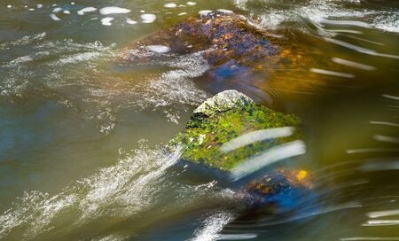 Abstract stream of muddy water flowing over green and brown boulder in wild river bed. Close-up of spring thaw. Playful light reflections, wet stones and white streamlines on rippled surface in creek.