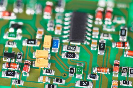 Green printed circuit board with surface mount technology of electronic components. Abstract close-up of microchip, small diodes, capacitors, resistors or transistors. Electrical engineering. E-waste. Banque d'images