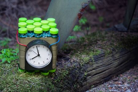 Improvised time bomb planted near metal device on old wood with green moss. Dangerous explosive device with timer or red and blue wire. Violent crime, terrorist act or military attack. Terrorism, war. Zdjęcie Seryjne