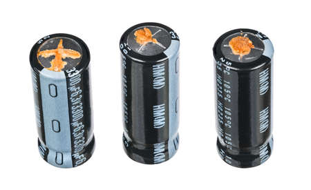Bad swollen aluminum electrolytic capacitors isolated on white background. Three condensators with grooves on metal top for bursting at overpressure and leaked electrolyte. High ESR. Electronic waste.