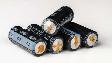 Aluminum electrolytic capacitors with failure from disuse on a white background. Pile of electrical condensers with leaked electrolyte fluid. Damaged passive electronic components. E-waste. Side view.