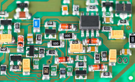 Close-up of semiconductor electronic components with surface mount technology. Green printed circuit board detail. Small resistors and transistors or diodes and capacitors. Electrotechnical industry.