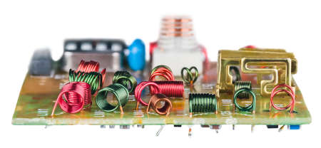Colored wire winding of air core coils in circuit board on white background. Various red or green RF inductors on disassembled device for receiving high-frequency analog television signal. Side view.