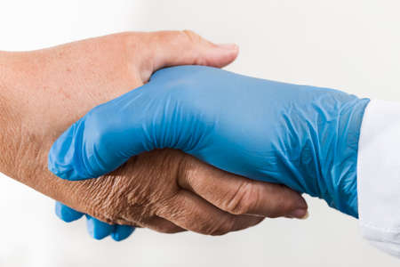 Helping hand of health professional holding old wrinkly palm on white background. Detail of safe handshake of doctor in blue protective glove and senior patient. Elderly care concept in pandemic time.