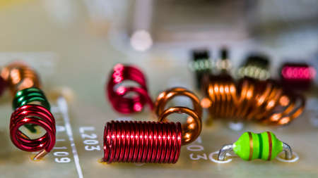 Close-up of colored air-core coils wire windings for receiving radio-frequency signal. Circuit board detail with RF electronic inductors inside dismantled TV device module. Side view. Selective focus.