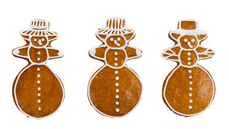 Set of sweet gingerbreads in snowman shape isolated on white background. Close-up of three cute cookies decorated by icing. Handmade pastry for Xmas or Children's day celebration. Baked child toy.