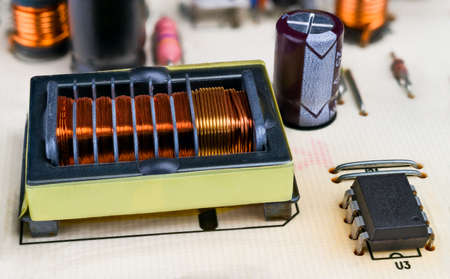 Copper wire winding in transformer rectangular core and protruding insulation grooves. Closeup of electronic componets on PCB detail. Integrated circuit, capacitor or induction coils. Electrotechnics.