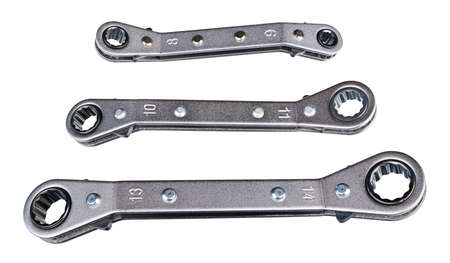 Set of ratcheting box-end wrenches or ring spanners isolated on white background. Close-up of double head ratchet handles. Three various sized metal hand tools for screwing and tightening nut or bolt.