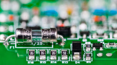 Electrical glass fuse or resistors, diode and transistor on printed circuit board in artistic detail. Small safety device soldered to green PCB and electronic components with surface mount technology.