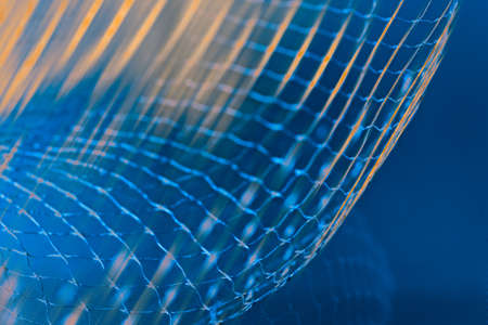 Dynamic detail of abstract airy net and orange light rays on blue background. Beautiful mesh of azure toned fibers on rastered texture in navy shade. Artistic grid for technology, research or science. 免版税图像