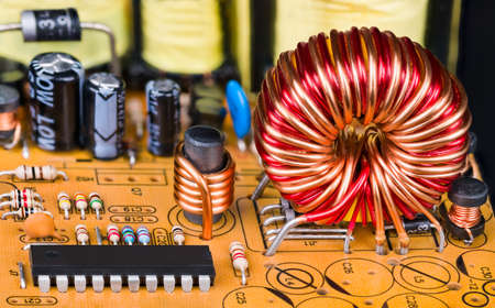 Toroidal or cylindric inductors on printed circuit board with electronic components. Closeup of magnetic core coils, microchip and resistors or capacitors on orange PCB detail. Electrical engineering. Banque d'images