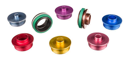 Set of aluminum router template guide bushings isolated on a white background. Colorful copying rings and green nuts for wood milling. Woodworking tool accessory with colored anodizing surface finish.