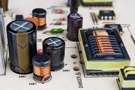 Electronic components on printed circuit board detail. Close-up of capacitors, inductors and rectangular transformer with protruding insulation grooves in copper wire winding. Electrical engineering.