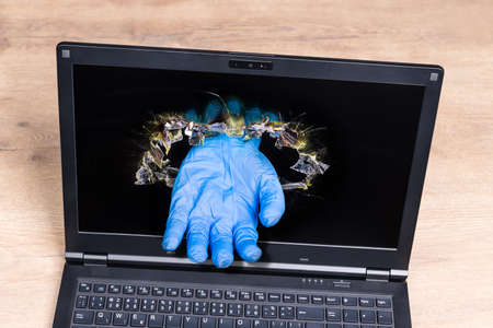 Laptop detail with imaginary helping hand in blue glove sticking out of punched hole in display. Online medical help idea. Symbolic virtual doctor. Distance health care concept in  disease.