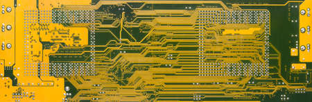 Printed circuit board panoramic background on computer hardware card. Back side of yellow multilayer PCB with green solder stop mask and high density interconnects. Line pattern on electronic texture.