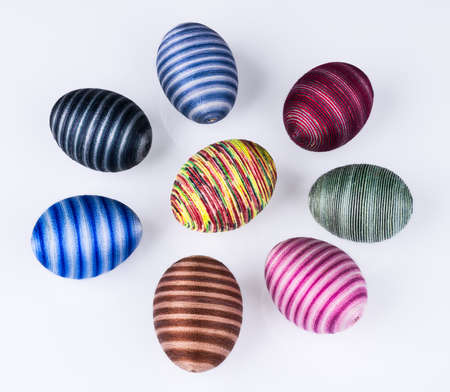 Group of colored Easter eggs with striped pattern on a white background. Collection of hollow shells hand-decorated by pasted sewing cotton yarn. Set of various streaked holiday decorations. Top view. Stock Photo