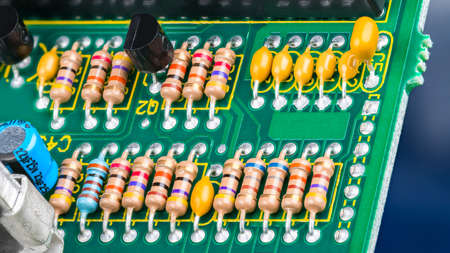 Closeup of printed circuit board with electronic components. Electrotechnics. Colorful resistors with standard color code, yellow or blue capacitors and black transistors on green PCB detail. E-waste.