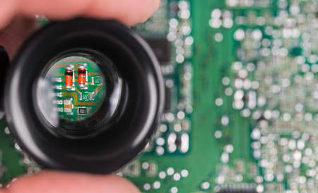 Small electronic components in black loupe on green PCB background. Closeup of magnified red semiconductor diodes, resistor or capacitors in hand lens on blurry printed circuit board with white bokeh.