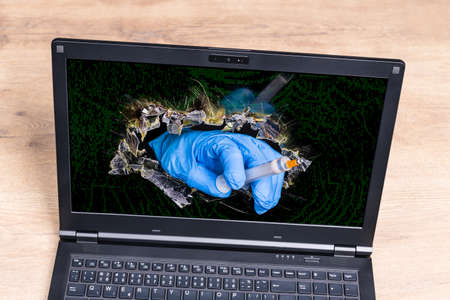 Syringe with   vaccine in doctor hand sticking out of broken laptop desktop. Virtual healthcare professional inside hole in digital monitor. Concept of hope for  disease vaccination.