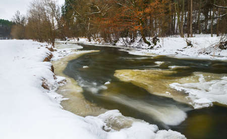 Winter landscape with dynamic flow of Lomnice river in South Bohemia nature. Wild riverbed with white snow and trees on shore and beautiful motion blur of fresh running water surface with melting ice.