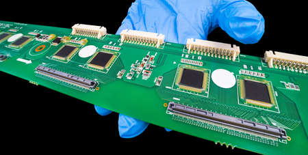 Long electronic printed circuit board on hand in blue glove isolated on a black background. Surface-mount technology on green PCB detail with white connectors and chip pins in protective silicone gel.