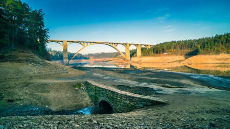 High arched viaduct across empty Orlik dam and original bed of Vltava river. Contrast of big modern concrete and small old stone road bridge at bottom of discharged artificial lake. Podolsko, Czechia.
