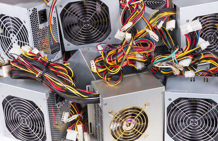 Detail of old power supply units heap as electrical background. Metal boxes stack of discarded computer hardware spare parts with fans, colorful cable bundles and white connectors. E-waste separation. Stock Photo