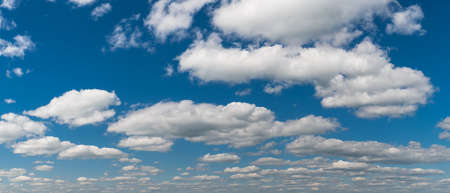 Beautiful white clouds on blue sky in panoramic natural background. Abstract cloudscape scenery with floating fluffy cumuli on azure heaven in scenic panorama. Water cycle, climate change and ecology.