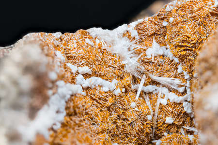 Detail of orange and white aragonite with clusters of crystals on black background. Close-up of beautiful texture of mineral from calcium carbonate. Collectable item: Hridelec near Nova Paka, Czechia.