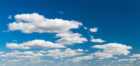 Group of idyllic floating white clouds on azure blue sky background. Tranquil natural panoramic cloudscape scene with copy space in top right corner. Environment or ecosystem, weather and meteorology. Stock Photo