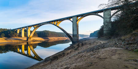 Long concrete road bridge over empty Orlik dam with original Vltava river bed. Beautiful sunny panorama with arched viaduct across riverbed and blue sky reflection in water surface. Podolsko, Czechia.