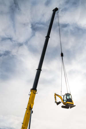Hydraulic crane telescopic boom detail moving a track excavator on cloudy sky background. Yellow jib of mobile vehicle hoist device carrying small earthmover. Building machine high up in white clouds.