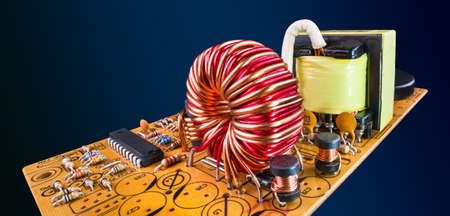Electronic components in orange circuit board flying on dark blue background in abstract scene. Ferrite core coils, resistors and a chip or transformer on PCB detail in panoramic artistic still life. Stock Photo
