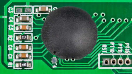 Integrated circuit with epoxy glop-top coating placed directly on a green PCB detail. Chip on board and surface-mount technology. Small electronic components inside dismantled electric voltage tester. 免版税图像
