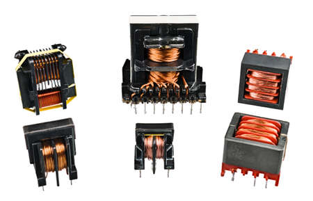 Set of isolation transformers with copper wire on inductors isolated on a white background. Electromagnetic coils in device for transfer energy in electrical circuits. Electronics industry components.