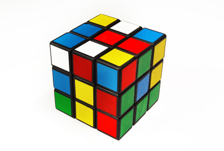 Colorful and world famous Rubik's cube in a scrambled state on a white background