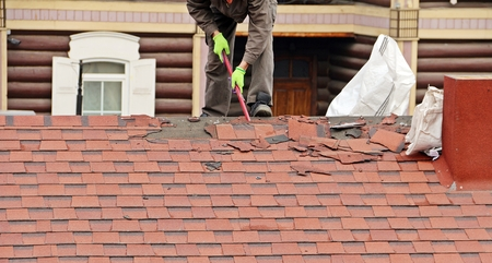 Worker in proper outfit repairing red tile on the roof Banque d'images