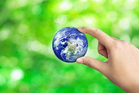 Hand, die Erde auf grünem Bokeh-Naturunschärfehintergrund hält, das Weltkonzept retten Standard-Bild