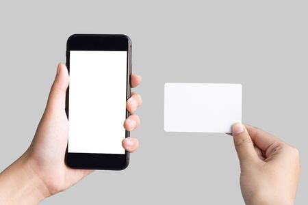 two hands holding smart phones and empty white card on white background
