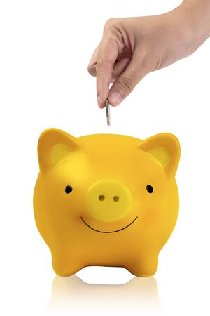 women hand putting coin into yellow piggy bank isolated on white.vertical image