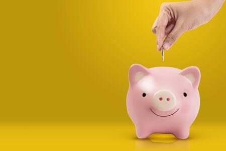 women hand putting coin into pink piggy bank on yellow background Reklamní fotografie