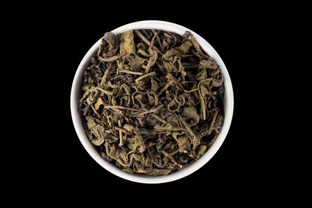 top view of dry green tea in bowl isolated on black background