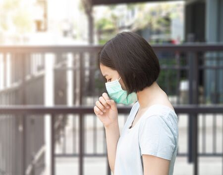 Asian woman wearing mask and cough sneeze on blurred background with sunlight Reklamní fotografie